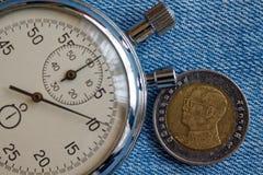 与十在蓝色牛仔裤背景-企业背景的泰铢(后部)和秒表的衡量单位的泰国硬币 库存图片