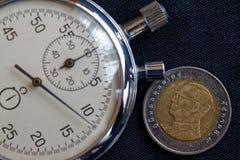 与十在黑牛仔布背景-企业背景的泰铢(后部)和秒表的衡量单位的泰国硬币 免版税库存照片