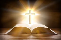 与十字形的垂饰的圣经在木板条做的桌前面 免版税库存图片