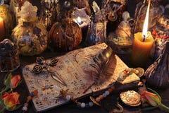 与十字架、纤管、灼烧的蜡烛和不可思议的瓶的巫婆书在桌上 图库摄影