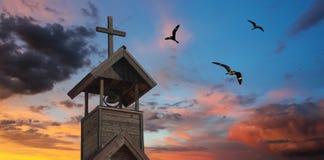 与十字架和夜生活者的一座钟楼 免版税库存照片