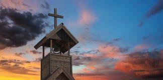 与十字架的一座钟楼在日落 图库摄影