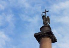 与十字架的天使反对多云蓝天 库存图片
