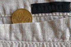 与十欧分的衡量单位的欧洲硬币在亚麻布裤子的口袋的有黑条纹的 免版税库存图片
