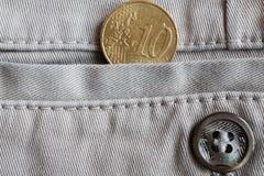 与十欧分的衡量单位的欧洲硬币在白色牛仔布牛仔裤的口袋的有按钮的 免版税库存照片