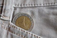 与十泰铢分的衡量单位的泰国硬币在老米黄牛仔布牛仔裤的口袋的 库存图片