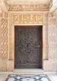 与华丽被镀青铜的花卉样式的闭合的木年迈的门在默罕默德阿里Tewfik,开罗,埃及王子Manial宫殿  库存图片