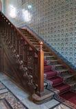 与华丽隆重,装饰的木楼梯栏杆和土耳其陶瓷砖墙壁的上升的木楼梯 库存图片
