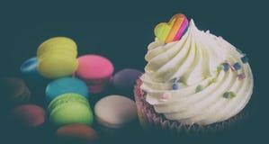 与华伦泰彩虹心脏上面的杯形蛋糕 免版税库存照片