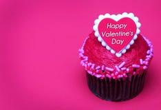 与华伦泰心脏的巧克力杯形蛋糕在上面,在桃红色 免版税图库摄影