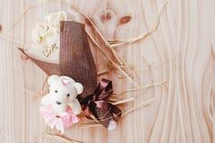 与华伦泰节日礼物美丽的净花束的白色和黄色玫瑰花和在花束的爱词与婴孩负担玩偶 免版税库存图片