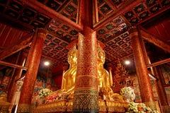 与华美的被上漆的柚木树木柱子的印象深刻的四方的供以座位的菩萨图象在Wat Phumin寺庙,楠府,泰国 免版税库存照片