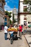 与卖果子的一个人的街道场面在老H的国会大厦附近 免版税库存图片