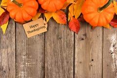 与南瓜和叶子顶面边界的愉快的感恩标记在木头 免版税库存照片