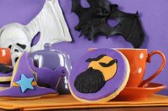 与南瓜和飞行棒装饰的愉快的万圣夜党把戏或款待紫色和橙色曲奇饼 免版税库存图片