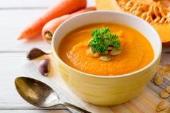 与南瓜籽和荷兰芹的南瓜和红萝卜奶油色汤在白色木背景的碗 库存照片