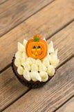 与南瓜蛋糕轻便短大衣的万圣夜杯形蛋糕在一张老土气木桌上 免版税库存照片
