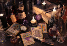 与占卜用的纸牌、刀子、书和蜡烛的静物画在巫婆桌上 库存图片