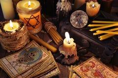 与占卜用的纸牌、蜡烛和书的神秘的静物画 免版税图库摄影