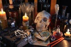 与占卜用的纸牌、头骨和灼烧的蜡烛的不可思议的静物画 库存图片