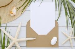 与卡片模板的大模型信封在白色木背景 热带棕榈叶、夏天帽子、seastars和壳 免版税库存图片
