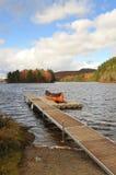 与印地安独木舟的秋天风景在船坞 库存照片