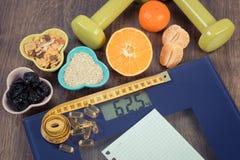 与卷尺的数字式标度,片剂,哑铃,果子, muesli,减肥概念 免版税图库摄影