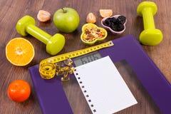 与卷尺的数字式标度,片剂,哑铃,果子, muesli,减肥概念 库存图片