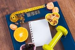 与卷尺的数字式标度,片剂,哑铃,果子, muesli,减肥概念 库存照片