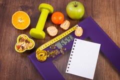 与卷尺的数字式标度,片剂,哑铃,果子, muesli,减肥概念 免版税库存照片
