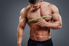 与卷尺的爱好健美者测量的胸口 库存图片
