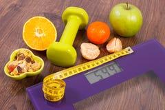 与卷尺,哑铃,果子, muesli的数字式标度,减肥概念 免版税库存照片