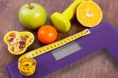 与卷尺,哑铃,果子, muesli的数字式标度,减肥概念 库存图片