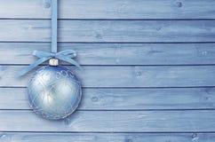 与卷曲丝带的蓝色圣诞节中看不中用的物品在有拷贝空间的一个蓝色木板 简单看板卡的圣诞节 免版税库存照片