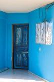 与卷毛的装饰品在蓝色门 库存图片