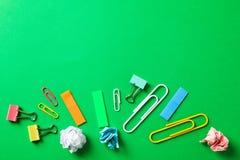 与压皱纸球、夹子和贴纸的平的被放置的构成在颜色背景 免版税图库摄影