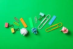 与压皱纸球、夹子和贴纸的平的被放置的构成在颜色背景 库存图片
