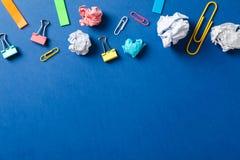 与压皱纸球、夹子和贴纸的平的被放置的构成在颜色背景 图库摄影
