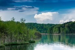 与厚实的桦树森林和好的蓝天的湖风景 免版税图库摄影