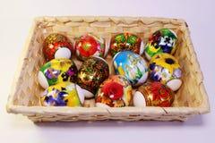 与原始的绘画的复活节彩蛋在桌上的篮子 库存图片