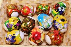 与原始的绘画的复活节彩蛋在桌上的篮子 免版税库存照片