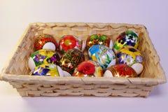 与原始的绘画的复活节彩蛋在桌上的篮子 免版税库存图片