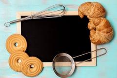 与厨房器物、黄油曲奇饼/饼干、新月形面包和被构筑的黑板的平的位置设计在小野鸭绿色土气背景, 免版税库存照片
