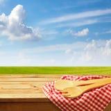 与厨房器物的木桌在绿色草甸和蓝天 库存照片