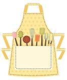 与厨房器物的被加点的厨房围裙在 免版税库存图片