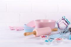 与厨房工具的烘烤背景:滚针,木匙子,扫,筛, bakeware和形状在白色的曲奇饼切削刀 免版税库存照片