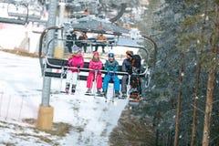 与去在滑雪地形的升降椅的家庭 免版税图库摄影