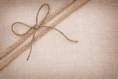 与去对角地在织品背景的二条绳索的一个蝶形领结 免版税库存照片