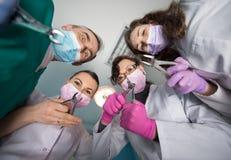 与去膜剂的专业牙齿队在牙齿办公室 底视图 免版税库存图片