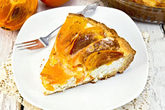 与叉子的饼用凝乳和柿子在板材在船上 免版税库存图片